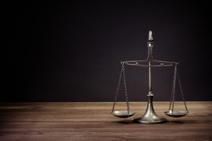 Law scales on table in front black background. Symbol of justice